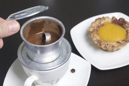 Vietnamese coffee maker is equipped on a cup. It is filled with ground coffee and pour boiling water. There is a cake on the saucer. The man lifted the lid of the brewer.