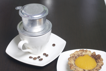 Vietnamese coffee maker is equipped on a cup. It is filled with ground coffee and pour boiling water. There is a cake on the saucer. Banco de Imagens - 96275943