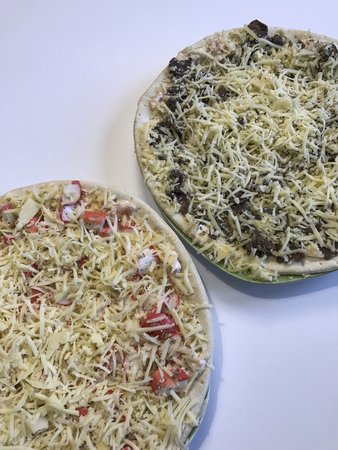 On the table are two pizza, ready to bake. One with mushrooms, the other with crab sticks. Both are covered with a thick layer of grated cheese. 版權商用圖片