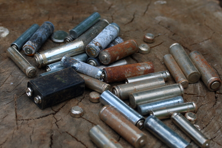 Spent batteries, coated with corrosion. Different shapes and sizes. lie on the edge of a wooden stump. Environmental protection, recycling. Banco de Imagens