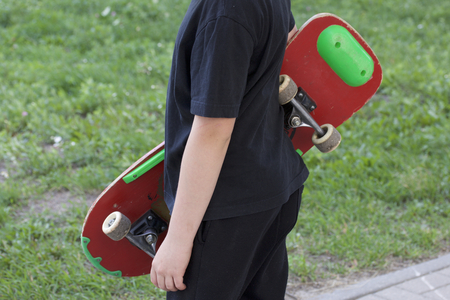A teenager with a skateboard. Holds a skate in the hands. Stock Photo