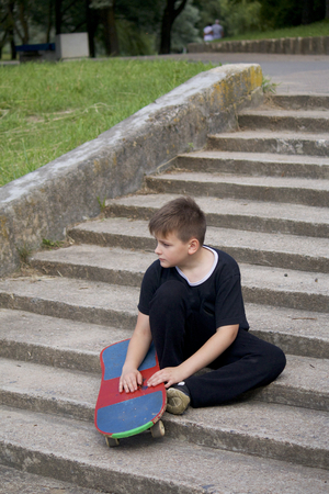 A teenager with a skateboard. Sits with a skateboard against the backdrop of a stone staircase. Stock Photo