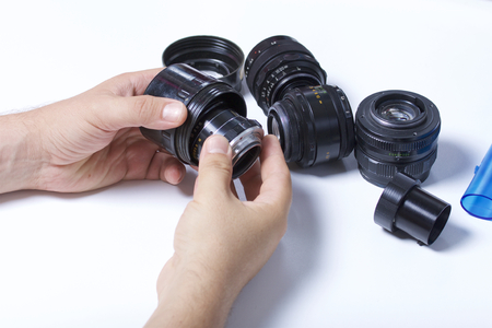 The man takes out the lens from the plastic case. Nearby on the table are other vintage lenses.