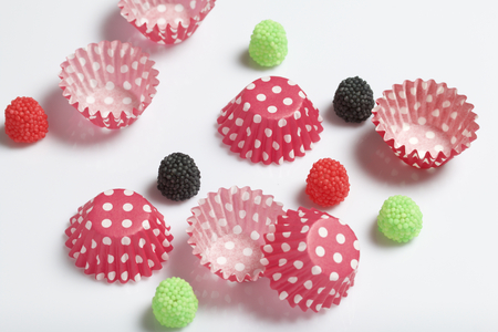 Decoration for baking in the form of raspberries. Different color. It is worth it among the molds for baking cakes. On a white background.