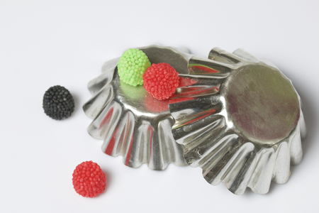 Decoration for baking in the form of raspberries. Different color. It is worth on inverted metal forms for baking cake. On a white background.