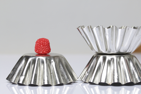 Decoration for baking in the form of raspberries. It is worth on inverted metal forms for baking cake. On a white background.
