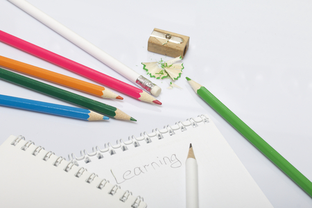 Stationery for school and teaching. Notepad and pencils for writing and drawing. Pencil sharpener with pencil shaving.