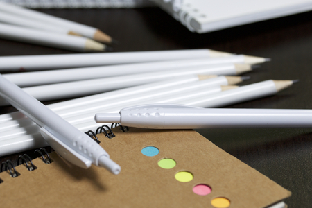 White spring pads, simple pencils and ballpoint pens for notes and sketches. Near a notebook of a different color. Stationery for school and teaching. On a dark background.