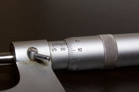 Micrometer with a circular scale for external measurements and a measuring range of 25 - 50 mm. On a dark background. Stock Photo