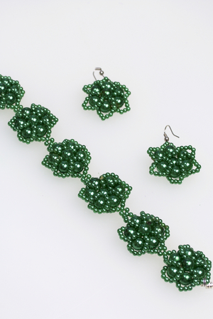 Earrings and bracelet handmade. Needlework at home. Bead jewelery. Green colour. On a white background.