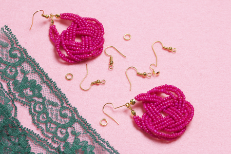Earrings from beads handmade. Pink colour. Nearby are scattered ear wires and other accessories. Needlework at home. Bead jewelery.