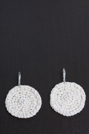 Earrings knitted with embroidery from beads. White color. Handmade. On a dark background.
