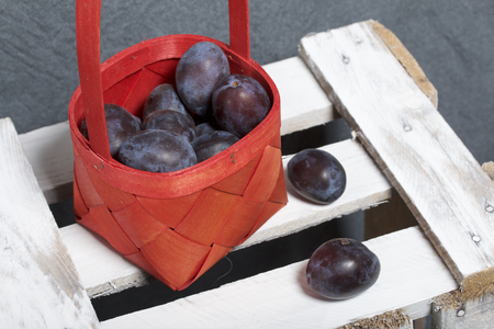 Ripe fragrant plums in a wicker basket. Located on a wooden box, knocked out of the boards.