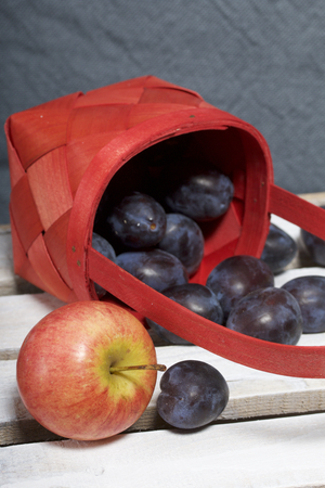 Ripe fragrant plums and apples crumbled out of a wicker basket. Located on a wooden box, knocked out of the boards.