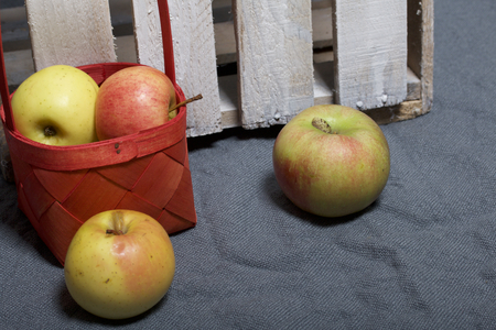 Ripe aromatic apples on a gray cloth. Nearby is a wooden box, knocked out of the boards. Stock Photo