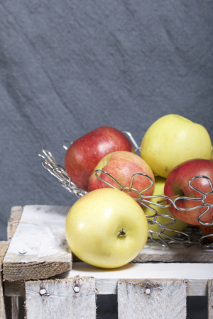 Ripe aromatic apples in a steel basket. Located on a wooden box, knocked out of the boards. Stock Photo
