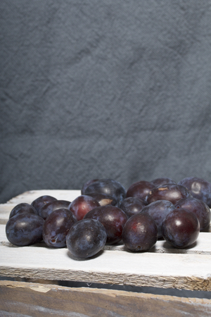Ripe aromatic plums. Located on a wooden box, knocked out of the boards.