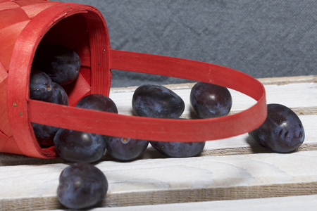 Ripe fragrant plums crumbled out of a wicker basket. Located on a wooden box, knocked out of the boards. Stock Photo