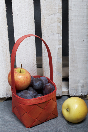 Ripe aromatic plums and apples in a wicker basket. Located near the wooden box knocked out of the boards.