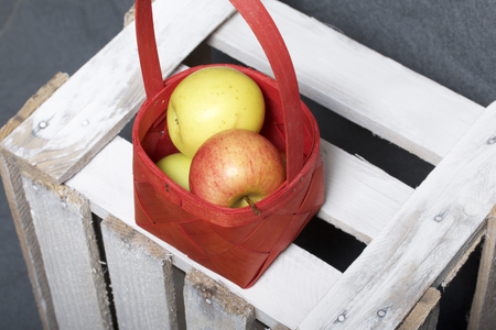 Ripe aromatic apples in a wicker basket. Located on a wooden box, knocked out of the boards. Stock Photo