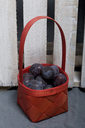 Ripe fragrant plums in a wicker basket. Located near the wooden box knocked out of the boards.