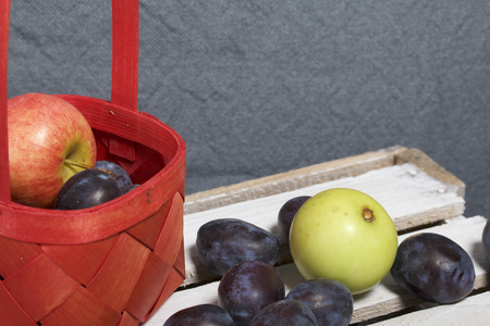 Ripe aromatic plums and apples in a wicker basket. Located on a wooden box, knocked out of the boards. Stock Photo