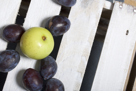 Ripe aromatic plums and apples. Located on a wooden box, knocked out of the boards.