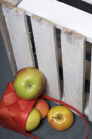 Ripe aromatic apples from a wicker basket on a gray cloth. Nearby is a wooden box, knocked out of the boards. Stock Photo
