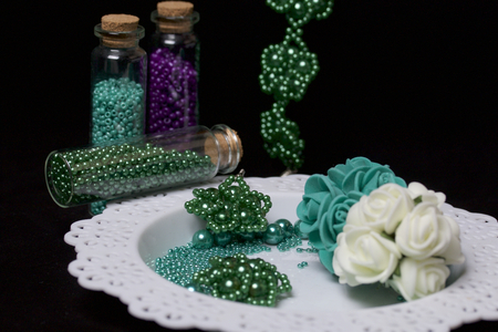 Bead jewelery. DIY jewelry. Necessary accessories. Beads and ready-made earrings. Tools and fixtures. On a black background.