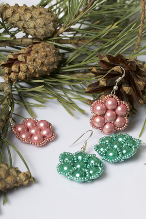 Women's earrings from beads among pine branches with cones. On a white background.