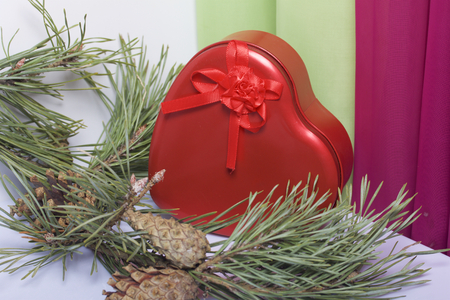 Red box with a gift. Made in the shape of a heart. Near pine branch with a cone. Against the backdrop of curtains of lime and lilac color.