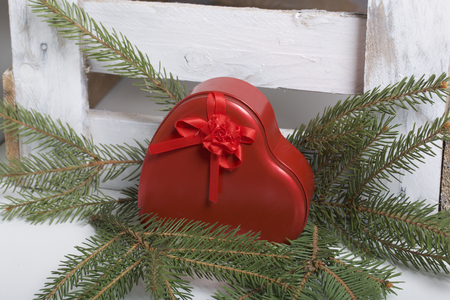 Red box with a gift. Made in the shape of a heart. Lies next to the wooden box. Near the fir branches. 版權商用圖片