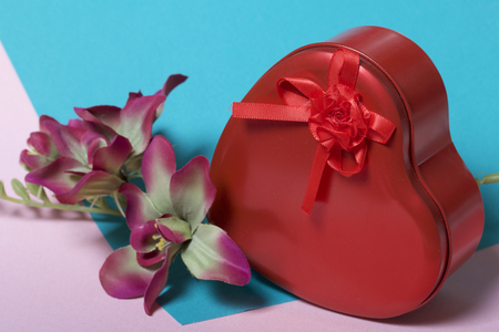 A box in the form of a red heart with a gift. Next is a flower. On a background of multicolored paper. 写真素材
