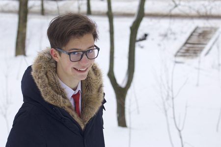Portrait of a young man in a coat with a fur collar. On a walk in the winter park. 写真素材