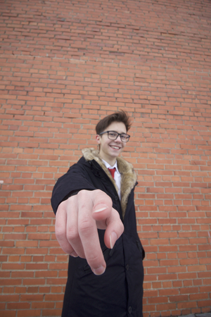 Portrait of a young man in a coat with a fur collar. Shows a finger in the lens. Shot with distortion on a wide-angle lens. On the background of a brick wall. 스톡 콘텐츠