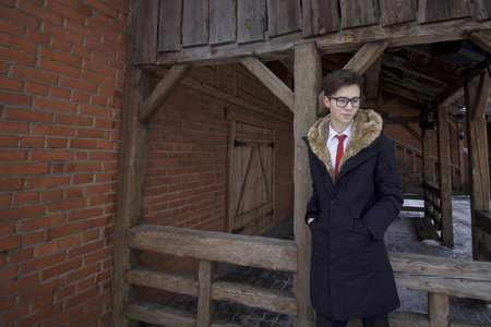 Portrait of a young man in a coat with a fur collar. Against the background of wooden construction in retro style.