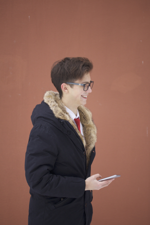 Portrait of a young man in a coat with a fur collar. Holds a smartphone in his hand.