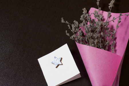 A bouquet of dried flowers, wrapped in colored paper. Near a small greeting card. On a dark background. Фото со стока