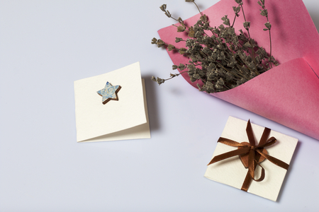 A bouquet of dried flowers, wrapped in colored paper. Near a small greeting card. On a white background. 스톡 콘텐츠