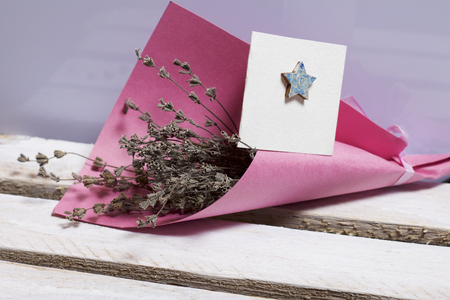 A bouquet of dried flowers, wrapped in colored paper. Near a small greeting card. 스톡 콘텐츠