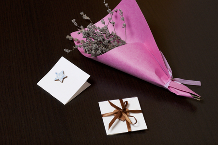 A bouquet of dried flowers, wrapped in colored paper. Near a small greeting card. On a dark background. 스톡 콘텐츠