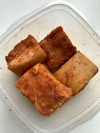 Pork lard with meat layer cut into pieces. Interspersed with salt and spices, lie in a container. 写真素材