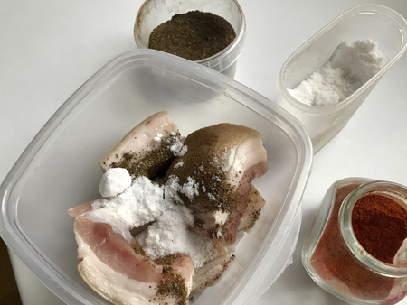 Pork lard with meat layer cut into pieces. Interspersed with salt and spices, lie in a container. Near salt, spices for salting lard. 写真素材