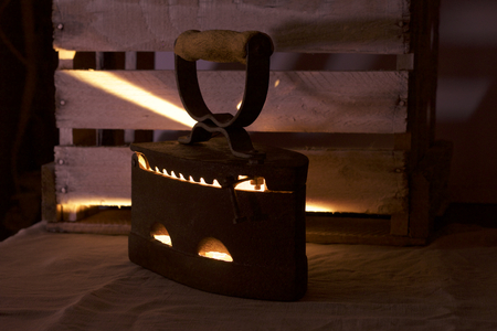 Old iron, heated by hot coals. In the twilight you can see the light of burning coals. Standing next to a wooden box.