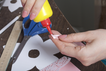 Making greeting cards from paper, cardboard and tape. Woman artisan working with glue.