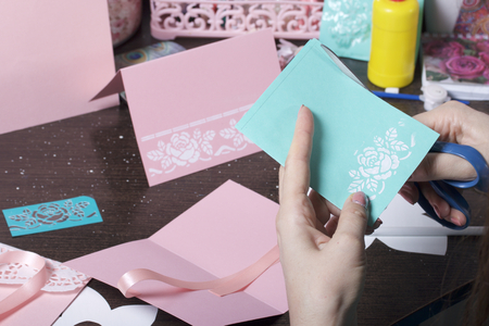Making greeting cards from paper, cardboard and tape. Female artisan working with tape. Фото со стока