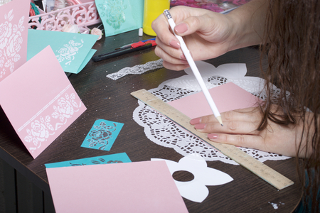 Making greeting cards from paper, cardboard and tape. Woman artisan makes a markup with a pencil.