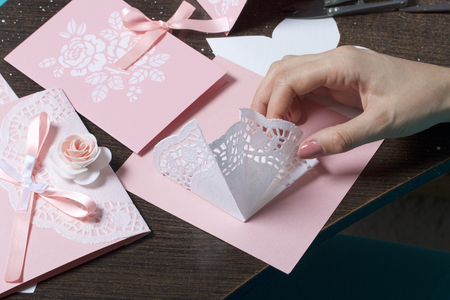 Making greeting cards from paper, cardboard and tape. Woman artisan at work.