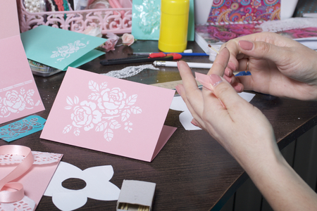 Making greeting cards from paper, cardboard and tape. Female artisan working with tape. 版權商用圖片