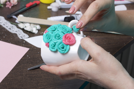 Crafts from polymer clay. A woman sticks a gummed polymer clay flower to a cup. Mug decorated with stucco made of polymer clay